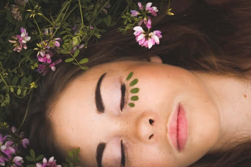 Swiss Wellness Day Spa Facial Treatments and Facial Services - Woman Lying with Flowers and Tattoos Botanical Facial